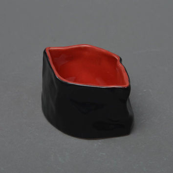 Handmade red and black porcelain sauce bowl painted with glaze in Japanese style