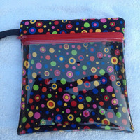 Vinyl see through padded zippered case is versatile. 7 1/2 in x 7 3/4 Made with black cotton material with bright circles in various colors.