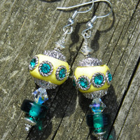 Pale yellow beads decorated with teal rhinestones dangle earrings