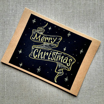 Hand lettered 'Merry Christmas' gold and black greeting card, blank holiday Kraft card, Christmas card with banner.