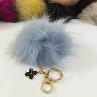 Fur pom pom keychain, bag pendant with flower charm in light blue with white markings color tone