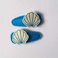 Cream and teal Seashell felt snap clip barrettes with dark teal snap clip covers. This is a set of 2 for $5.50.