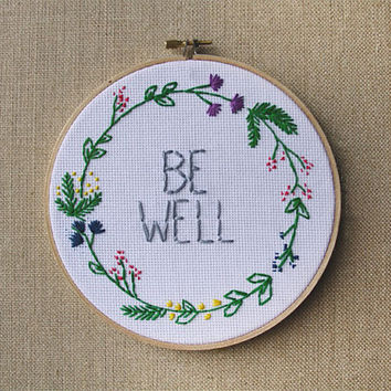 "Be Well Spring Wreath 7"" Round wood cross stitch with optional text. Custom made."
