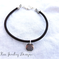 Lotus flower charm. Leather cording and sterling silver metal bracelet.