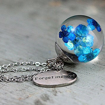Floating bright forget me nots in resin orb. Silver colored necklace with forget me not charm.