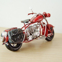 Red motorcycle miniature, retro collectible miniature  of a red, vintage bike with black saddlebags on the sides