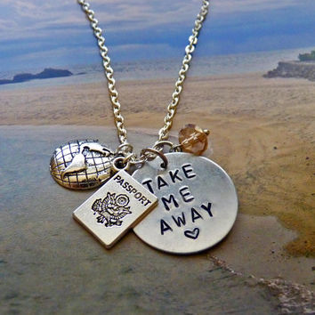 "Official Wanderlust necklace: Hand stamped ""Take Me Away"" metal tag, globe, passport charm, and crystal bead accent."
