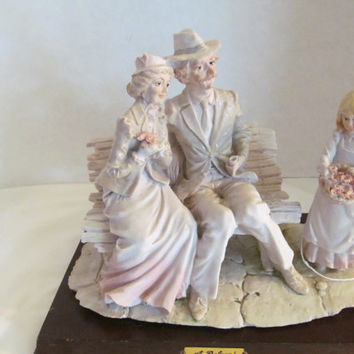 A Belcari figurine Older couple on park bench Dear Arnart Imports 1984 on wooden plaque