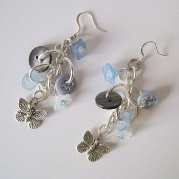 Attractive Button Dangle Earrings with Butterfly Charms, Acrylic Flowers, and Swarovski Crystal details in Pale Blue and Gray Hues