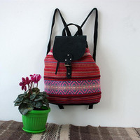 Ladies handmade backpack with black suede leather and unique handwoven textile in pink, red and white
