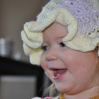 Hand knit pixie hat with lace, ruffle and crochet flower detail