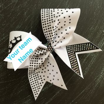 White bow with rhinestones and glitter designs. Leave. Anote with the name yoi want on the bow