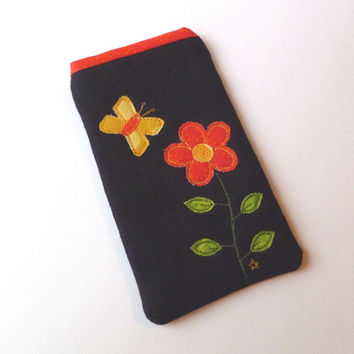 Embroidered phone case with flower and butterfly design in vibrant yellow and orange on black linen with orange star patterned lining.