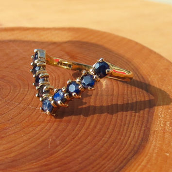 A vintage 9k yellow gold round cut white stone and sapphire wishbone ring