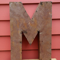 "Rusted Metal Letter ""M"" Crafted From Recycled Tin."