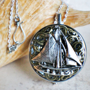 Music box locket, round silver tone locket with music box inside, with a nautical theme featuring a sailboat on front cover.