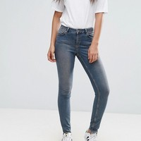 ASOS TALL LISBON Skinny Mid Rise Jeans in Dita Tinted Mid Wash with Reverse Stepped Hem at asos.com