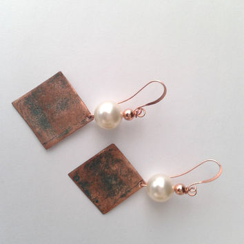 ethnic handmade earrings of on the front engraved  and patinated copper with a cream swarovski pearl of 12 mm and a