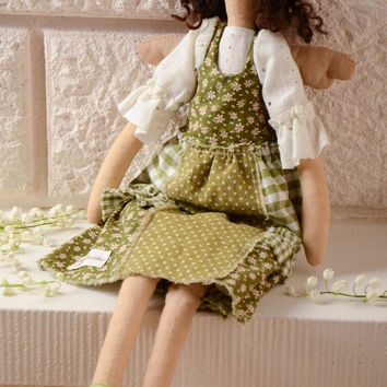 Handmade soft doll sewn of natural fabrics with curly hair in green dress