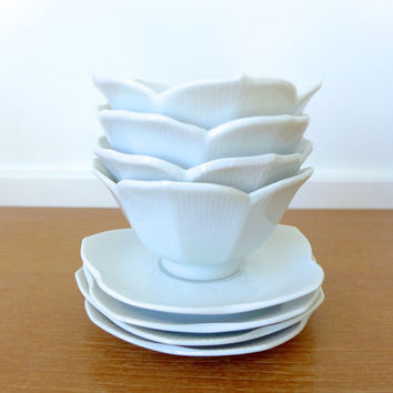 Four white lotus bowls with matching saucers