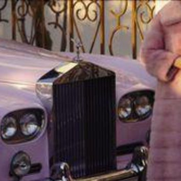 A woman wearing a pink mink coat stands next to her pink Rolls Royce.