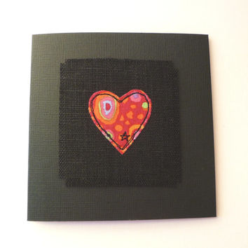 Handmade valentine card with embroidered red heart design on black textured card. Embroidered heart greetings card. Made in the UK.