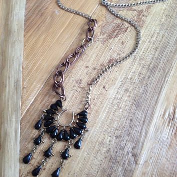 Black cab and gold necklace