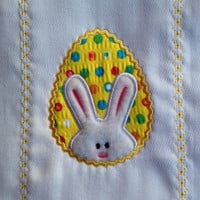 Burn cloth with a white bunny on a bright yellow polka dot egg. Can be personalized for and extra charge.