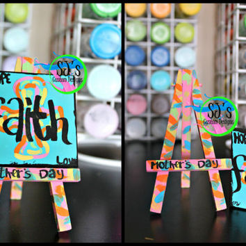 Mini canvas with a Cross and the words: Hope, Faith, and Love painted across it.