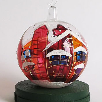Hand-painted Christmas blown- glass ball in a gift box. For Christmas and New Year's tree decoration. Christmas ornament. Red houses.