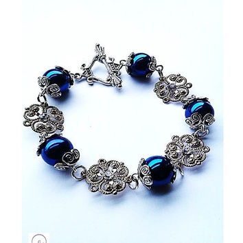Metallic Blue Bead And Thin Gold Plated Flower Pendant Bracelet With Vintage Clasp