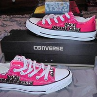 Hot pink womens Converse All Stars lowtop with silver studs along the outside of the s