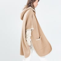 Hooded cape with piping