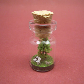 Cats are around a little bench in front of the tree in a tiny bottle