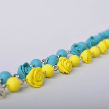 Handmade bright wrist bracelet with blue and yellow cold porcelain rose flowers