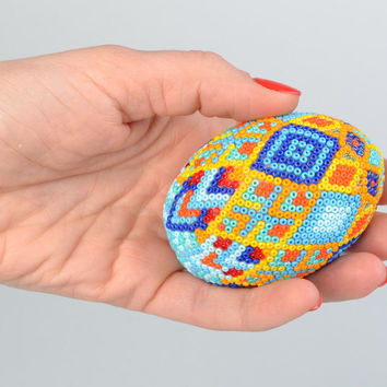 Handmade wooden multicolored Easter egg braided over with beads in Huichol style