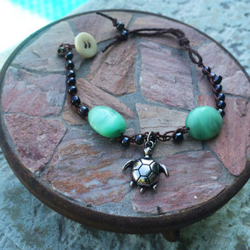 Green Peaking Eye Bracelet Crocheted with black glass beads and a silver turtle charm clasped together with a vintage bead and tassel