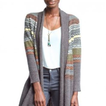 Lovely open front sweater cardigan featuring multicolor pattern at upper body, open front with lapel shawl, long sleeves, and asymmetrical hemline at front panel. Unlined. Pair with skinny jeans and Freebird by Steven Coal Boots.