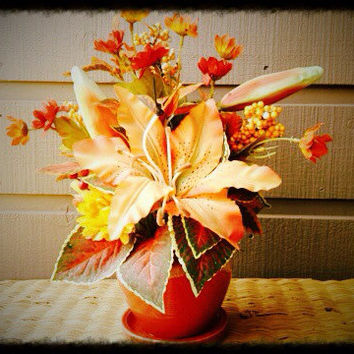 A treat to make you smile Autumn inspired orange Lilly  Floral Arrangement setting in a hand crafted orange and tan ceramic pot.
