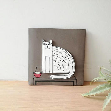 Sitting cat wall hanging, porcelain cat in grey background, square wall tile of stoneware and porcelain, sitting cat art object