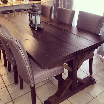 Beautiful, handmade, wooden, farmhouse table. The table is stained with all natural coffe stain and finished so that it has a rustic vibe.