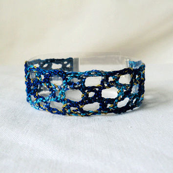 bracelet, handmade bobbin lace out of bead yarn, blue and gold, silver fastener, laurinke no 1016