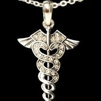 From the Heart Clear Crystal Sparkling Rhinestone Caduceus Pendant on 18 inch chain.Pendant is approximately 2 inches long.Caduceus is a Medical Symbol with Two Snakes Wrapped on a Rod in Different Directions with Wings on the Top. The Roots of this Symbol