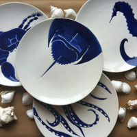 Set of 4 navy blue, nautical, beach themed ceramic dinner plates in horse shoe crab, octopus, blue crab and sea horse