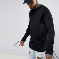 ASOS Oversized Long Sleeve T-Shirt With Lace Up Sleeves In Black at asos.com