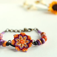Macramè colorful textile bracelet with mandala flower and beads orange liliac