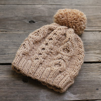 Knit beanie hat in beige color with cables and pom pom