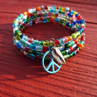 Bohemian rainbow memory wire bracelet, a rainbow of glass beads with peace sign and wing charms forms a hippie memory wire bracelet, peace