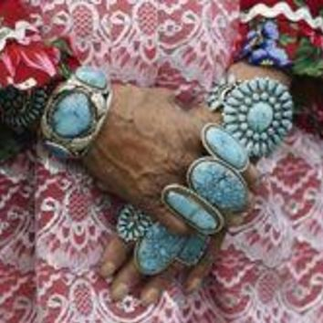 Heirloom rings and bracelets lie thick on arms and hands of Zuni woman