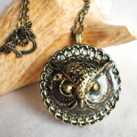 Music box locket, round bronze locket with music box inside, with a bronze filigree and a bronze owl on front cover.